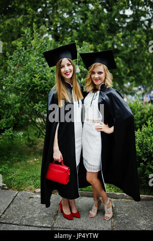 Two amazing young female graduates standing outside in graduation gowns and caps. - Stock Photo