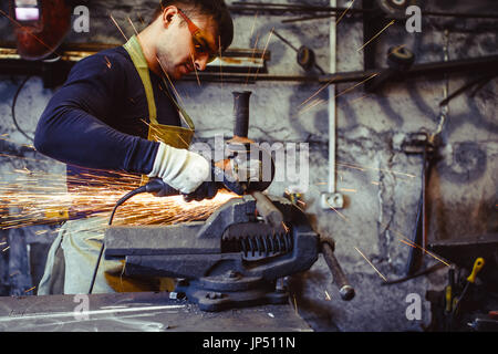 Craftsman sawing metal sparkles all around workshop. Working at noon. - Stock Photo