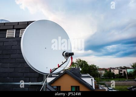 Satellite dish, satellite antenna mounted on the chimney of a new home. Evening - Stock Photo