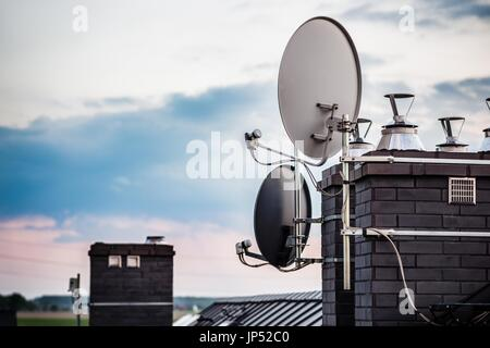 Satellite dishes, satellite antennas mounted on the chimney of a new home. Evening - Stock Photo
