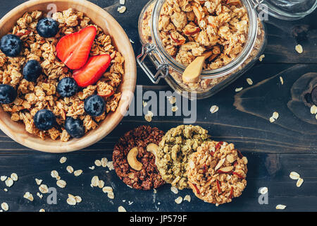 Homemade granola and fresh berries on wood table with space. - Stock Photo