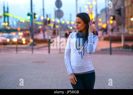 A beautiful young woman wearing sportswear and standing on the street in the city lights at night falls - Stock Photo
