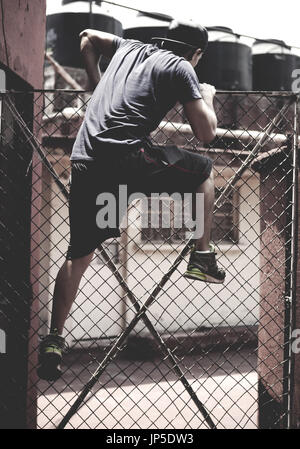 Young man climbing over a chain link fence in an urban environment. - Stock Photo