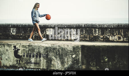 Young woman walking on a wall bouncing a basketball. - Stock Photo