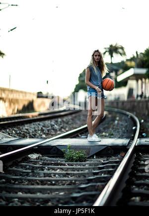 Young woman standing on railway tracks holding a basketball. - Stock Photo