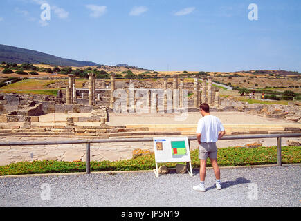Man reading the information sign. Roman ruins of Baelo Claudia, Tarifa, Cadiz province, Andalucia, Spain. - Stock Photo