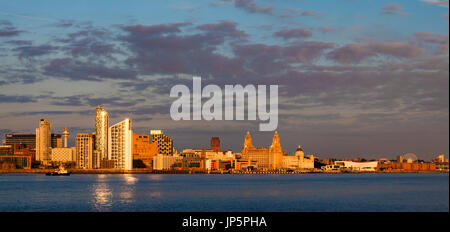 Golden glow Liverpool waterfront panorama taken just before dusk across the River Mersey at Seacombe. - Stock Photo