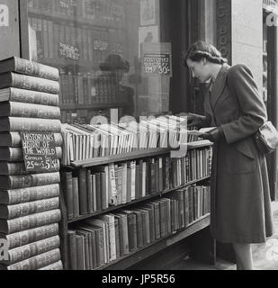 1948, Historical, England, Charing Cross Rd, London, a young lady browses the rows of second-hand hardback books - Stock Photo