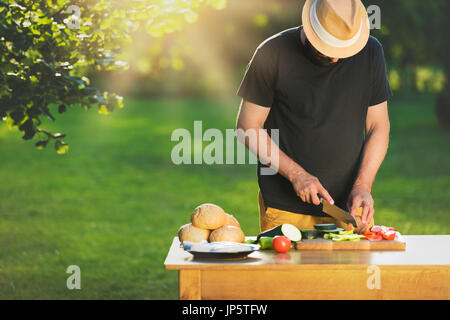 Young hipster man preparing food for garden grill party, summer barbecue concept - Stock Photo