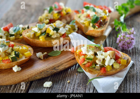 Warm vegetarian canapes: Baked crostini with mixed Greek vegetables with feta cheese served on a wooden cutting - Stock Photo