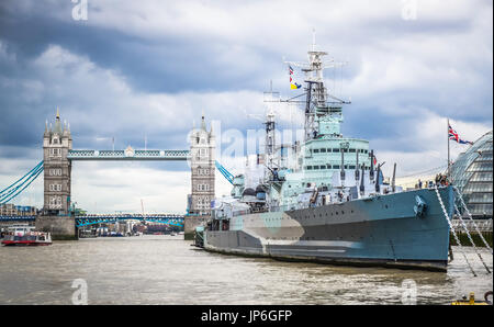 Royal Navy Cruiser HMS Belfast moored in Thames with Tower Bridge in Background - Stock Photo