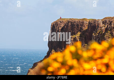 Person sitting on top of cliff near Giant's Causeway, Northern Ireland - Stock Photo