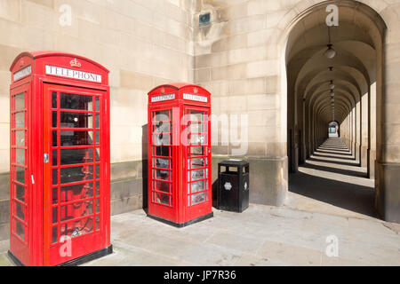 Classic British view in Manchester of old colonnades from the Manchester Town Hall Extension and iconic Red Phone - Stock Photo