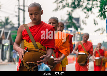 LUANG PRABANG, LAOS - MARCH 12, 2017: Horizontal picture of young monks going in line to Buddhist Alms Giving Ceremony, - Stock Photo