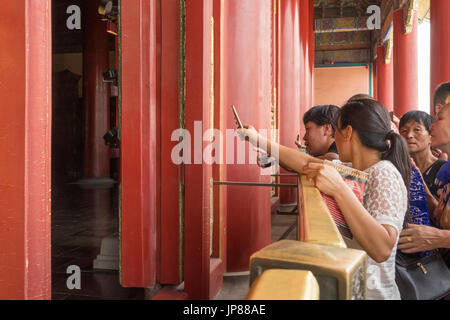 Chinese tourists clamboring to get a glimpse and take a mobile phone photo of the Hall of Supreme Harmony in the - Stock Photo