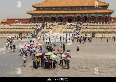 Tourists holding shade umbrellas approaching the Hall of Supreme Harmony in Forbidden City in Beijing China - Stock Photo