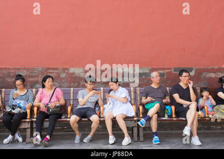 Chinese tourists of different ages sitting on bench at Forbidden City in Beijing - some eating some on their mobile - Stock Photo