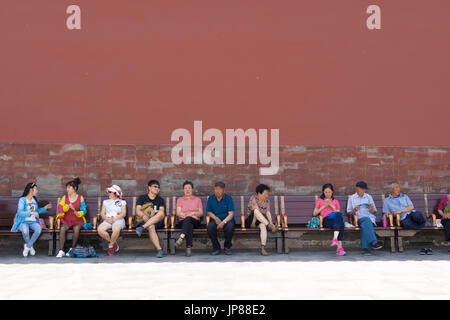 Chinese tourists of different ages sitting on bench at Forbidden City in Beijing - some resting, some talking, one - Stock Photo