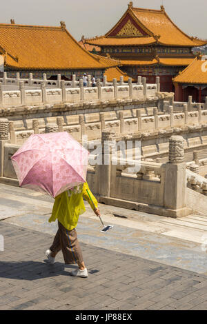 Woman holding shade umbrella and mobile phone with selfie stick walking by Palace of Heavenly Purity at Forbidden - Stock Photo