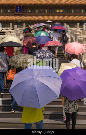 Tourists holding colorful shade umbrellas climbing up stairs to the Hall of Supreme Harmony in the Forbidden City, - Stock Photo