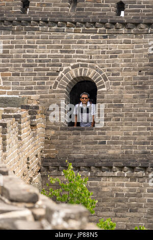 Indian tourist in his early 50s looking out from arched window at the Great Wall of China - Stock Photo