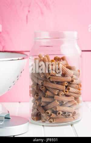 Dried rigatoni pasta in jar.  Dark semolina pasta. Uncooked pasta. - Stock Photo