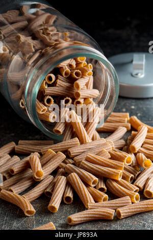 Dried rigatoni pasta in jar.  Dark semolina pasta. Uncooked pasta. - Stock Photo