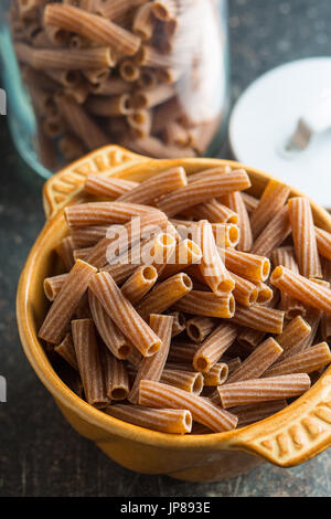 Dried rigatoni pasta in bowl. Dark semolina pasta. Uncooked pasta. - Stock Photo