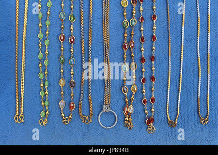 necklaces gold on blue cloth - Stock Photo