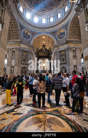 Vertical view of tourists lokking at Saint Peter's tomb inside St Peter's Basilica at the Vatican in Rome. - Stock Photo