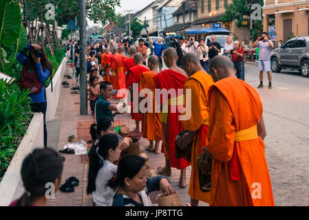 LUANG PRABANG, LAOS - MARCH 12, 2017: Horizontal picture of local people giving food and money to the monks for - Stock Photo