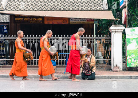 LUANG PRABANG, LAOS - MARCH 12, 2017: Lao woman on her knees giving to the monks food and money for the Buddhist - Stock Photo