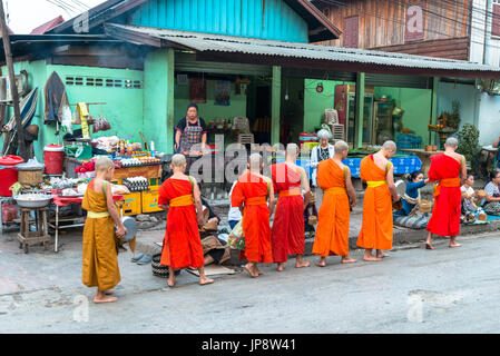 LUANG PRABANG, LAOS - MARCH 12, 2017: Wide angle picture of local people giving food and money to the monks for - Stock Photo