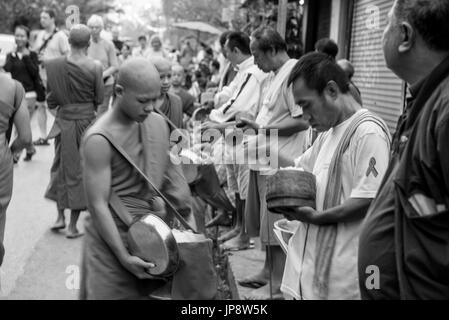 LUANG PRABANG, LAOS - MARCH 12, 2017: Black and white picture with movement of local people giving food and money - Stock Photo