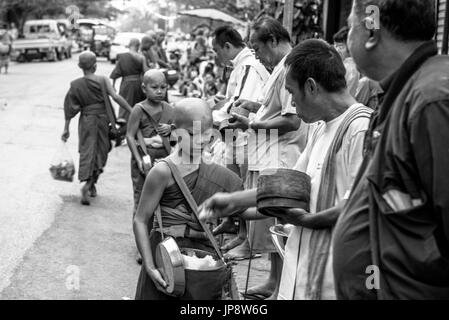 LUANG PRABANG, LAOS - MARCH 12, 2017: Black and white picture of local people giving food and money to the monks - Stock Photo