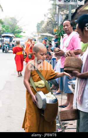 LUANG PRABANG, LAOS - MARCH 12, 2017: Vertical picture of young monk receiving foof for the Buddhist Alms Giving - Stock Photo
