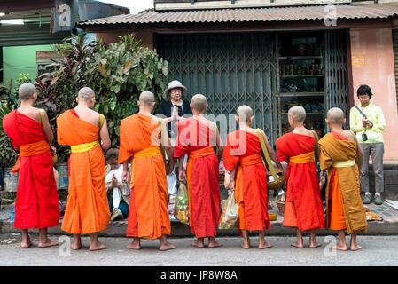 LUANG PRABANG, LAOS - MARCH 12, 2017: From back, Monks in line receiving food for the Buddhist Alms Giving Ceremony, - Stock Photo