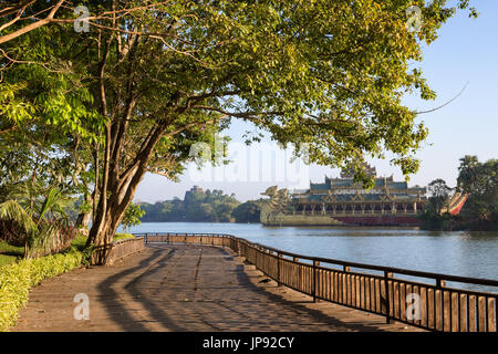 View of wooden boardwalk, lush trees and Karaweik at the Kandawgyi Lake in Yangon, Myanmar on a sunny day. - Stock Photo