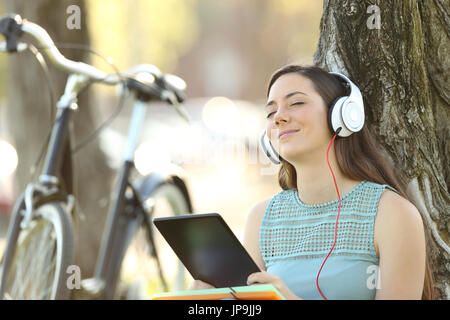 Single student wearing headphones listening to music on line with a tablet outdoors in a park - Stock Photo
