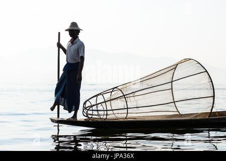 INLE LAKE, MYANMAR - FEBRUARY 15, 2014: Burmese fisherman on bamboo boat catching fish in traditional way with handmade - Stock Photo