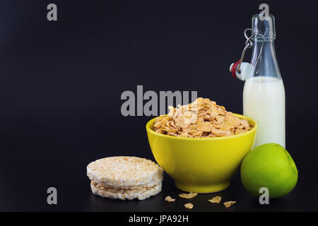 Energy breakfast for diet cereal flakes of corn milk and green apple on black background with copy space - Stock Photo