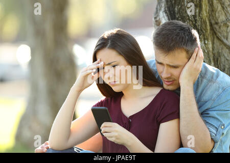 Worried couple using a smart phone to view on line content outside in a park - Stock Photo