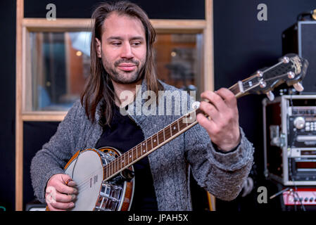 Musicians in the sound studio playing the banjo - Stock Photo
