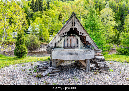 Petit-Saguenay, Canada - June 2, 2017: Wood log burning french fireplace by river in Quebec village - Stock Photo