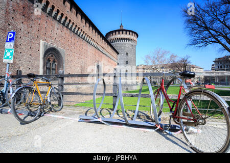 Bicycles parked at the entrance of the ancient Sforza Castle Milan Lombardy Italy Europe - Stock Photo
