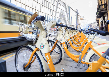 The deposit of city bikes sharing and the old yellow tram Milan Lombardy Italy Europe - Stock Photo
