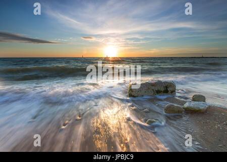 Waves crashing on the sandy beach framed by sunrise Porto Recanati Province of Macerata Conero Riviera Marche Italy - Stock Photo
