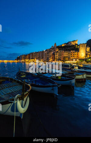 View of blue sea and boats surrounding the colorful village at dusk Portovenere province of La Spezia Liguria Italy - Stock Photo