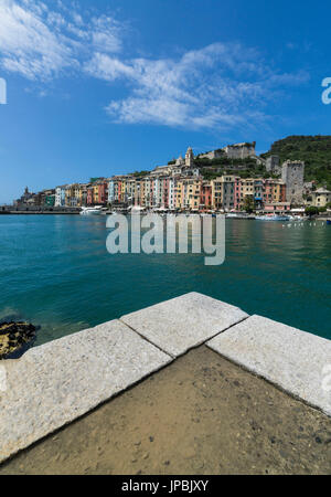 View from the pier of blue sea which frames the typical colored houses of Portovenere La Spezia province Liguria - Stock Photo