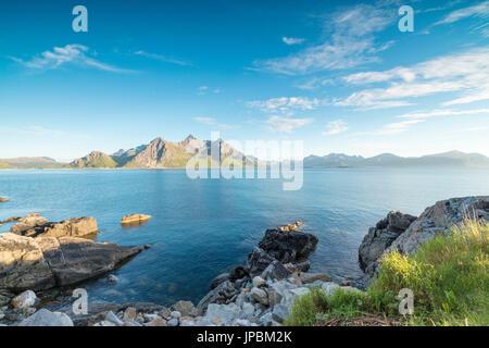 Sun shines on the blue sea and the rocky peaks at night during summer Vikten Nord Trøndelag Lofoten Islands Norway - Stock Photo